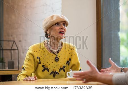 Old lady in cafe. Senior woman indoors. Tell me everything.