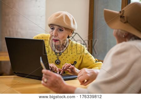 Senior ladies and laptop. Two old women indoors. Testing the touchpad.