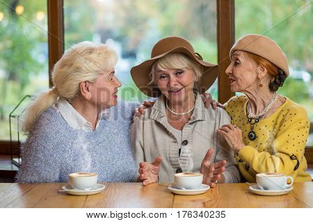Three senior women in cafe. Ladies talking and smiling. Meeting of childhood friends.
