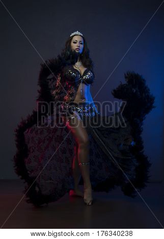Sexy woman, dancer, black stage costume with crystals