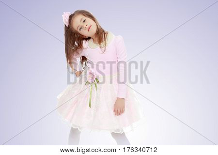 Dressy little girl long blonde hair, beautiful pink dress and a rose in her hair.She put forth a foot.Purple gradient background.