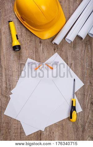 Screwdriver, protective glasses and helmet. Flashlight and architecture plans. Blank sheet of paper. Wooden rustic background.