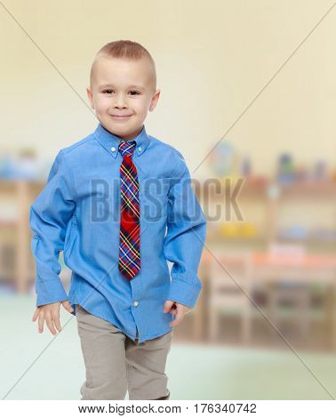 Cute little blonde boy in a Blue shirt and tie.In the Montessori room the children's garden where there are shelves with toys and material.