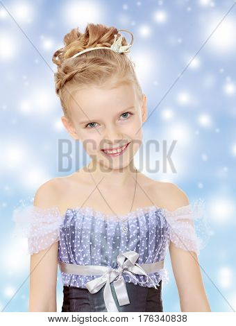 Slender little girl , with beautiful hair on his head, elegant long Princess dress.Girl smiling at the camera. Close-up.Blue Christmas festive background with white snowflakes.