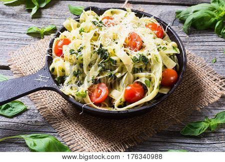 Pasta Tagliatelle with tomato and basil in pan .