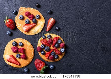 Pancakes with berries : blueberries raspberry and strawberry .