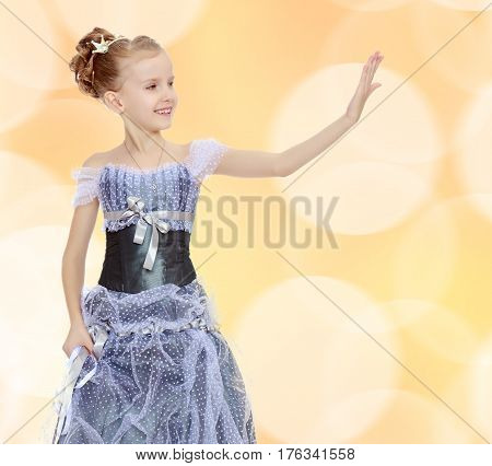 Slender little girl , with beautiful hair on his head, elegant long Princess dress.The girl stares at his palm like a mirror.