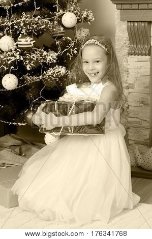 Cute little Princess white dressy holiday dress near the Christmas tree. Girl holding in hands a big box with a gift.Black-and-white photo. Retro style.