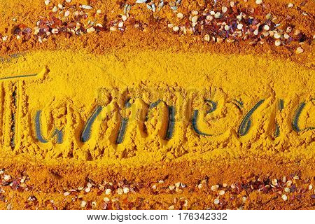 A background of turmeric powder and paprika powder with aother spices and text Turmeric in the center.