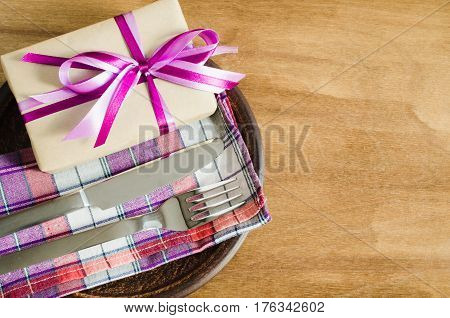 Festive Table Setting. Cutlery with Present on Linen Napkin on Rustic Wooden Background. Mother's Day Concept. Copy Space. Selective Focus.