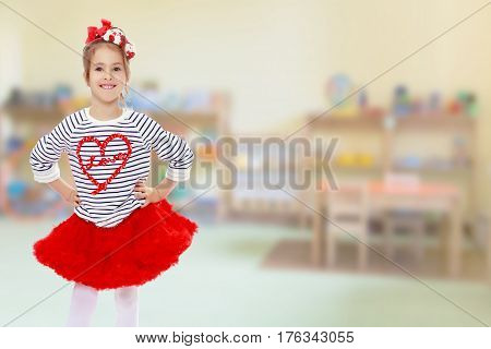 Portrait of a little girl in a bright red skirt with a red bow on his head.Girl standing with hands on hips.In the Montessori room the children's garden where there are shelves with toys and material.