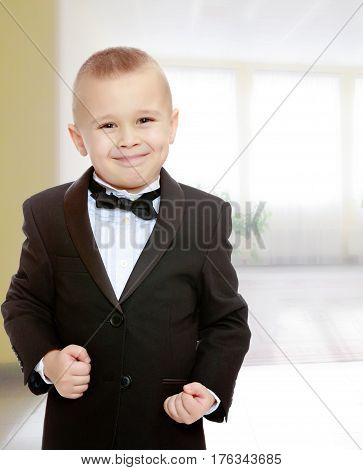 Beautiful little blond boy in a fashionable black suit with a tie.The boy tightly clenched his fists.In the Montessori room the children's garden where there are shelves with toys and material.