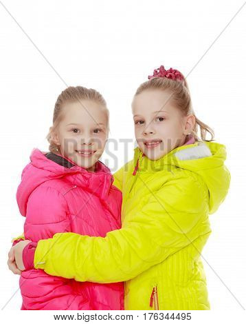Two charming twin girls in blazers pink and yellow.Isolated on white background.