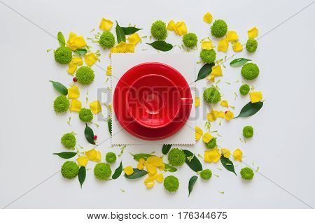 Cup for coffee or tea with pattern with petals of chrysanthemum flowers, ficus leaves  and ripe rowan on white background. Overhead view. Flat lay.