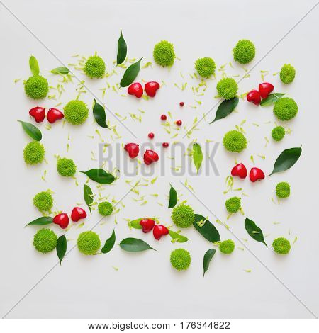 Hearts with pattern from petals of chrysanthemum flowers, ficus leaves and ripe rowan on white background. Overhead view. Flat lay.