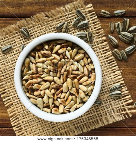 Roasted sunflower seeds in small bowl surrounded by whole seeds with hull photographed overhead on wood with natural light (Selective Focus Focus on the top of the roasted seeds)