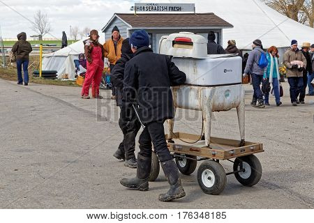 GORDONVILLE PENNSYLVANIA - March 11 2017: Amish boys deliver an old wringer washer for buyer at the annual spring auction