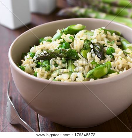 Green asparagus pea parsley and brown rice risotto served in bowl photographed on dark wood with natural light (Selective Focus Focus on the middle of the dish)