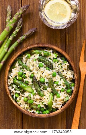 Green asparagus pea parsley and brown rice risotto served in wooden bowl photographed overhead on dark wood with natural light