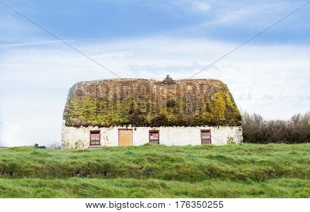 Old abandoned white house with a mossy roof. Ireland