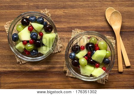 Fresh fruit salad made of cantaloupe melon blueberry redcurrant gooseberry and sweet cherry in glass bowls photographed overhead on dark wood with natural light (Selective Focus Focus on the top of the salad)