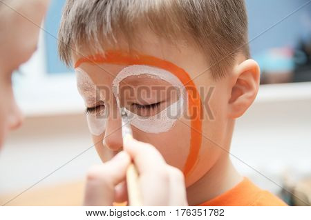 Make up artist making tiger mask for child.Children face painting. Boy painted as tiger or ferocious lion. Preparing for theatrical performance. Boy actor playing role. Tiger mask face
