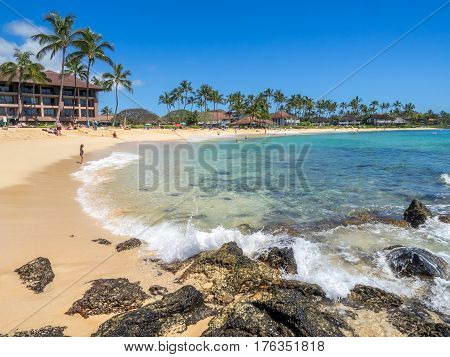 KAUAI, USA - MAR 5: Tourists and locals enjoy Poipu Beach on March 5, 2017 on Kauai, Hawaii. Poipu Beach is one of the most popular tourist areas on the island of Kauai and has many excellent hotels.