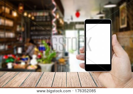 Mock up image of hand holding black mobile phone with blank white screen Empty wood table top on blurred images coffee shop for background perspective wood can be used for display products.