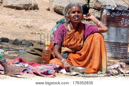 KEESRAGUTTA,HYDERABAD,INDIA-FEBRUARY 24:Indian senior blind woman seeks alms or begs on road to temple during Mahasivaratri festival on Frbruary 24,2017 in Hyderabad,India.