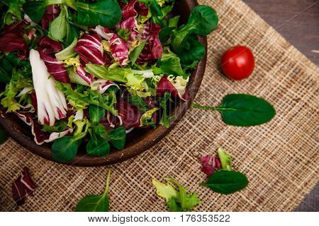 Provence salad. Leaves of endive or chicory, lamb and rose salad. Cherry tomato. Raw vegetables. On wooden table.