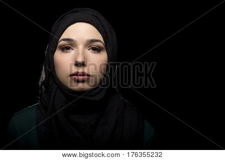 Proud and confident female wearing a black hijab as a conservative fashion choice to represent feminist freedom of expression and political statement. The headscarf is associated with muslims and middle eastern and east eauropean culture. poster