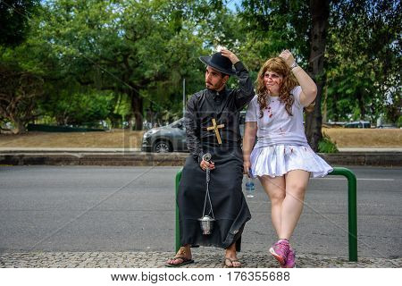 RIO DE JANEIRO, BRAZIL - FEBRUARY 28, 2017: Man in the costume of priest and woman with bleeding scratches on her face wearing white clothes with spots of blood sitting together at Carnaval 2017