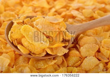 crispy corn flakes with wooden spoon and on pile of corn flakes