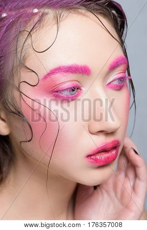 Woman with creative  pink colorful make-up. Beautiful brunette girl with pink brows and lashes glossy lips wet hair with perl