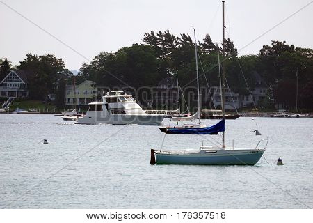 HARBOR SPRINGS, MICHIGAN / UNITED STATES - AUGUST 4, 2016: A yacht navigates past moored sailboats in the Harbor Springs Yacht Basin.