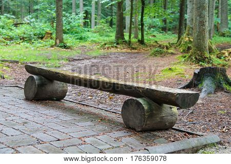 Wooden bench made of tree trunks in city park