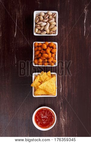 Nachos chips. Tortilla snacks with sweet salsa or chilli sauce. Exclamation sign concept. Mexican salsa and pistachios nuts. On rustic wooden background.