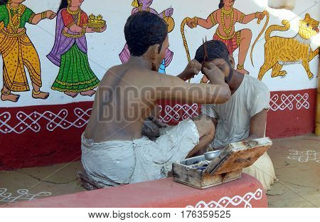 HYDERABAD,INDIA-MARCH 3 :Rural Indianr man a barber figurine do haircut in traditional way as seen in villages in Shilparamam on March 3,2017 in Hyderabad,India.