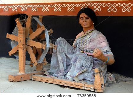 HYDERABAD,INDIA-MARCH 3:Rural Indian woman life sized figurine work on spinning wheel to make thread or yarn from natural or synthetic fibers in Shilparamam on March 3,2017 in Hyderabad,India.