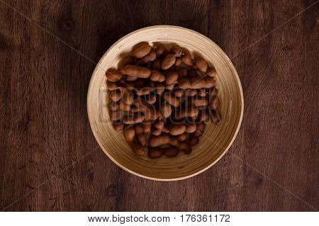 Sweet tamarind on grunge rustic wood background. Natural organic diet food with a lot of vitamins. Plate dish or bowl on wooden board.