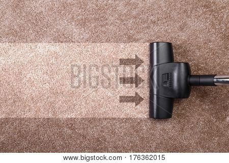 Vacuuming carpet with vacuum cleaner. Housework service. Close up of the head of a sweeper cleaning device. poster