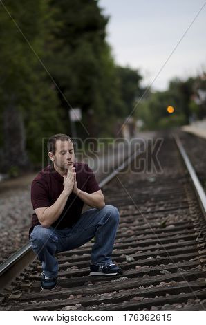 Man crouching to pray on rail road tracks.