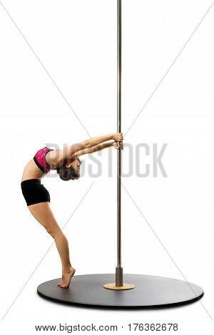 Slim girl in pink bikini streching by the pylon isolated studio shot