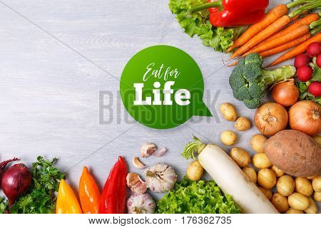 Vegetables. Potatoes, salad and carrot. Parsley, onion and garlic. Pepper, brocoli and white radish. Organic food on wooden table.