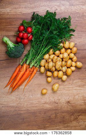 Potatoes with carrot. Red radish, brocoli and raw new potato. Fresh natural vegetables. Organic bio food. On wooden table.