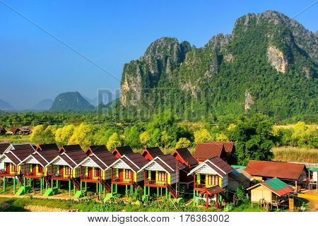 Row of tourist bungalows along Nam Song River in Vang Vieng Vientiane Province Laos. Vang Vieng is a popular destination for adventure tourism in a limestone karst landscape.