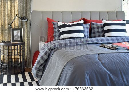 Modern Bedroom Interior With Striped Pillow On Bed And Bedside T