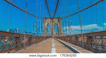 New York United States of America - June 2 2016: Panoramic view of the Brooklyn Bridge in New York NY one of the oldest suspension bridges in the United States with people on the bridge