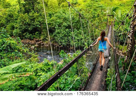 Young woman walking on suspension bridge over Wainibau stream Lavena Coastal Walk Taveuni Island Fiji. Taveuni is the third largest island in Fiji.