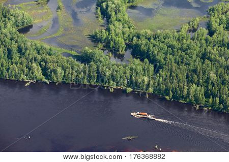 Aerial view of forest the river during summer day. The ship with barge moves along the river.